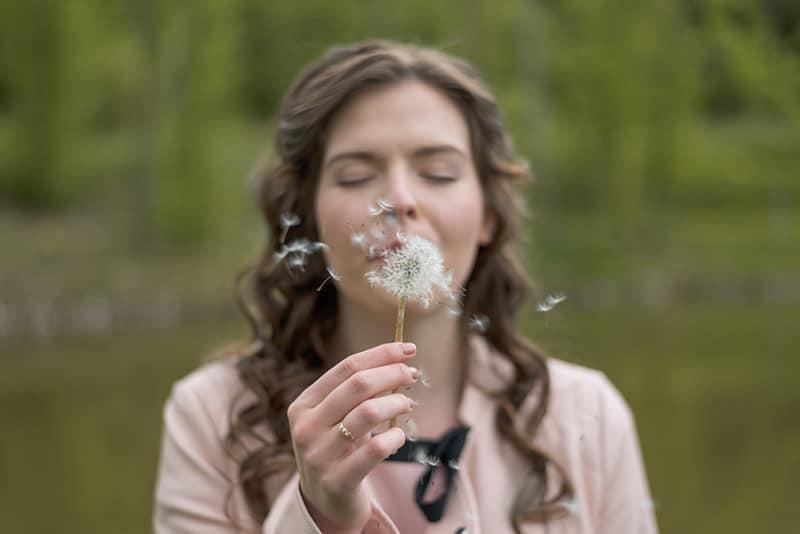 eine Frau, die Löwenzahnblume mit geschlossenen Augen bläst