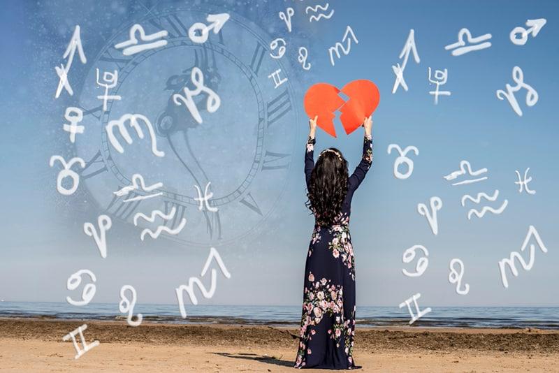 eine Frau, die Papierherz in der Luft hält, während sie am Strand steht