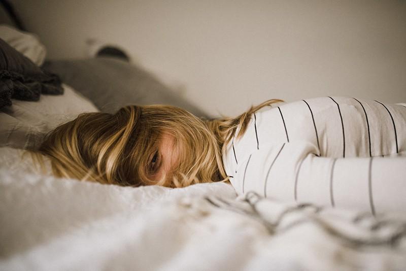 eine Frau, die auf dem Bett liegt und deren Kopf mit Haaren bedeckt ist