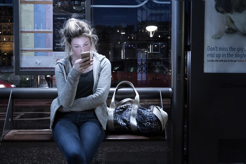 Eine Frau sitzt auf der Bank und versucht, einen Freund auf einem Smartphone an der Bushaltestelle zu kontaktieren