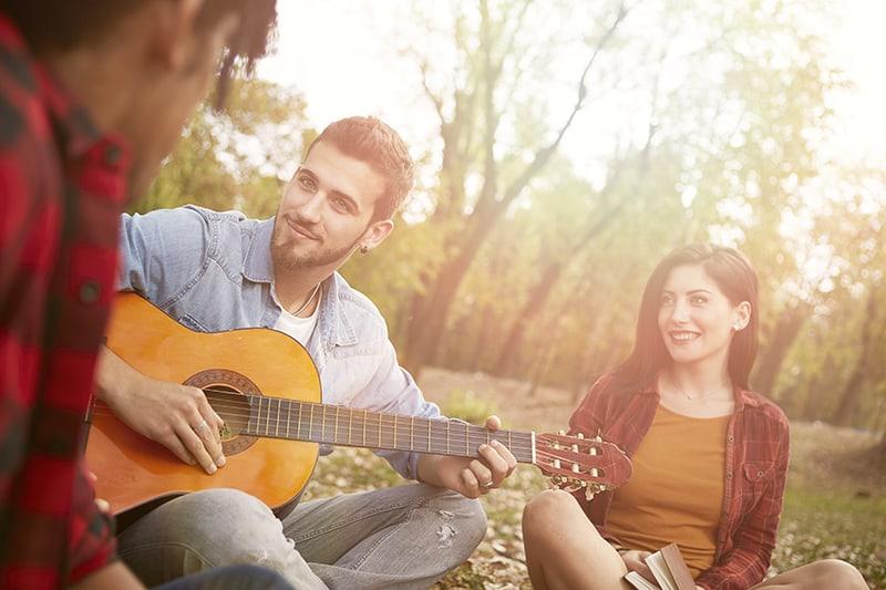 eine Frau, die zu einem Mann schaut, der unter Freunden Gitarre spielt