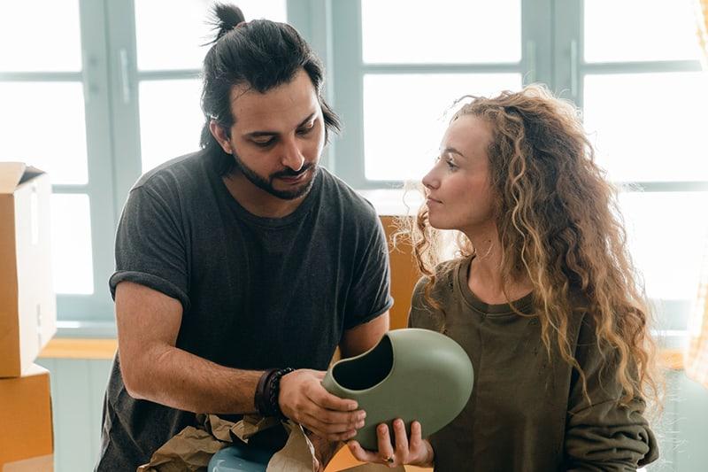 eine Frau, die auf einen Mann schaut, der die Vase hält und betrachtet, während er sie auspackt