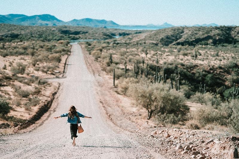 eine Frau, die mit ausgebreiteten Armen auf einem Feldweg geht