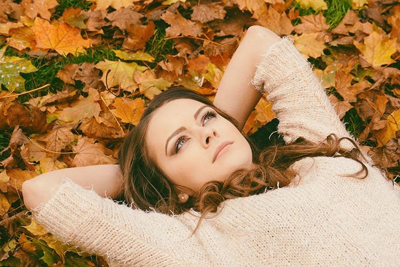eine Frau, die auf getrockneten Blättern liegt und aufschaut