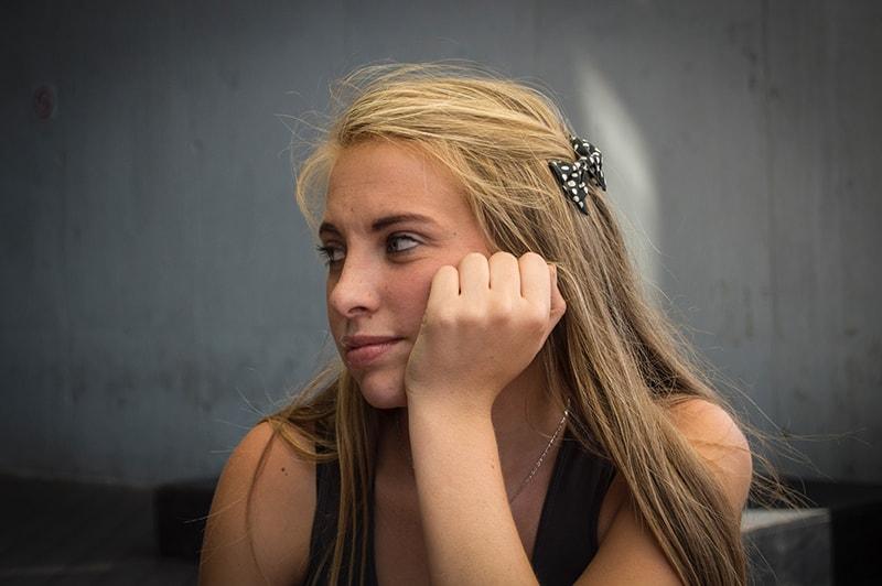 eine Frau, die auf ihre rechte Seite schaut und ihren Kopf auf die Handfläche lehnt