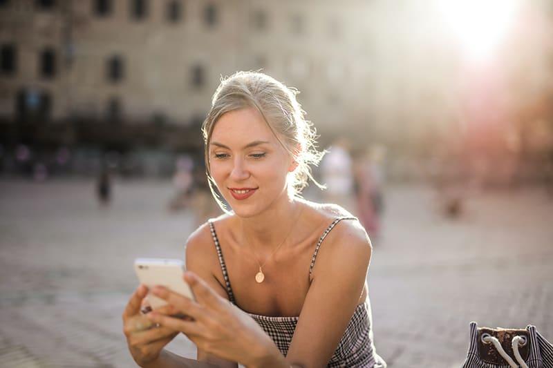 eine Frau, die auf ihrem Smartphone tippt, während sie auf dem Platz sitzt