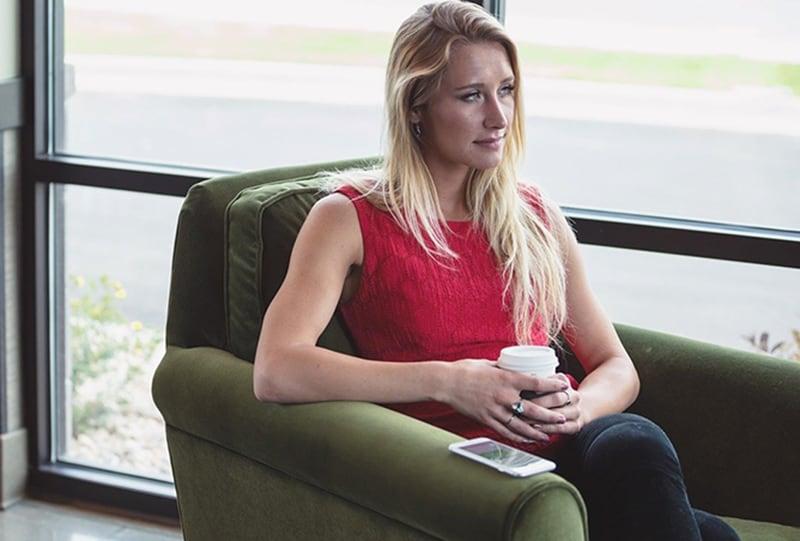 eine Frau, die durch das Fenster schaut und im Sessel sitzt, während sie nachdenkt