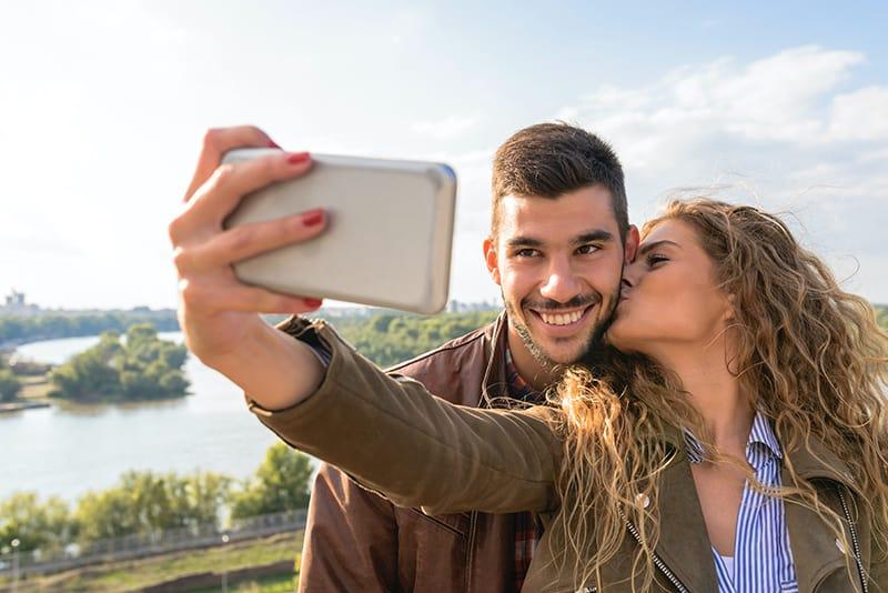 eine Frau, die mit ihrem Freund ein Selfie macht