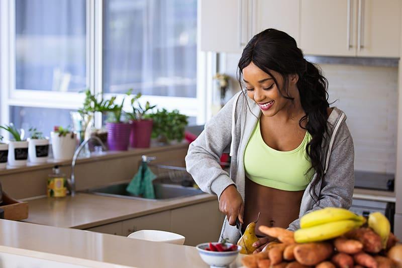 eine Frau, die eine Birne schneidet, während sie eine gesunde Mahlzeit in der Küche zubereitet