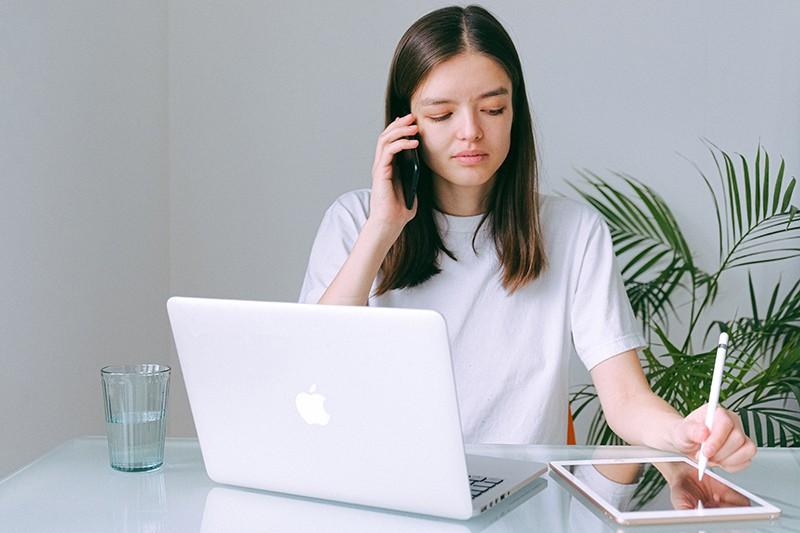 eine Frau, die einen Anruf hat, während sie im Büro sitzt