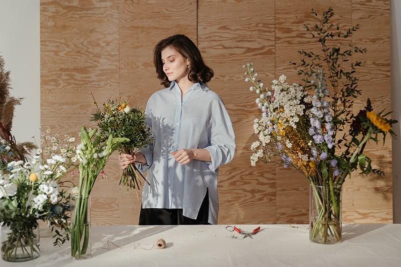 eine Frau, die einen Blumenstrauß macht, während sie in der Nähe des Tisches steht