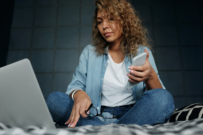 eine Frau, die einen Laptop benutzt und ein Smartphone hält, während sie auf dem Bett sitzt