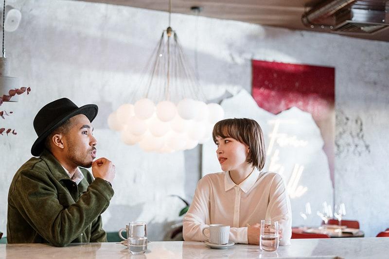 eine Frau, die einen Mann ansieht, der mit ihr spricht, während sie an der Theke im Café sitzt