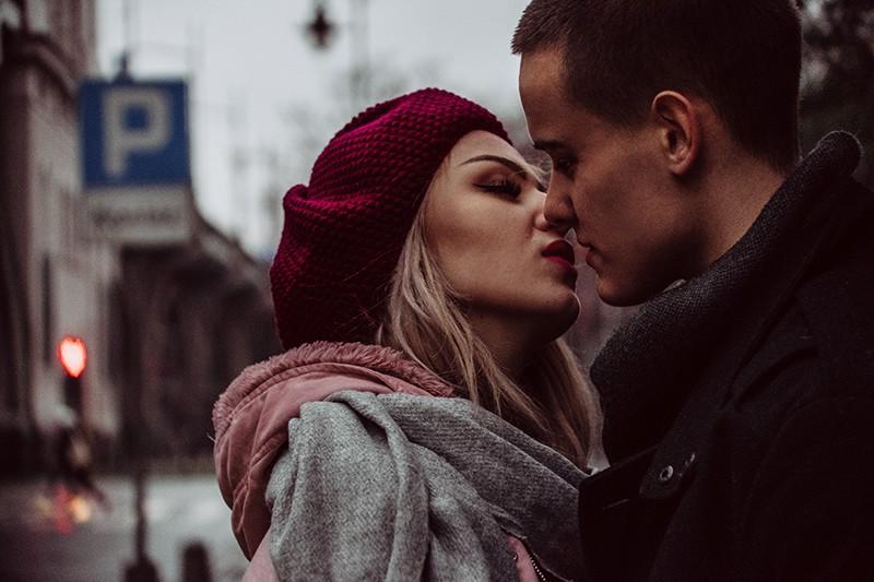 eine Frau, die gerade einen Mann küssen will, während sie zusammen auf der Straße steht
