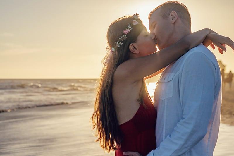 eine Frau, die einen Mann umarmt, während sie sich mit ihm küsst, während sie am Strand steht