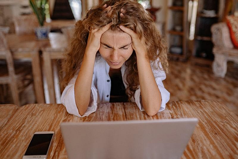 eine Frau, die frustriert aussieht und mit den Händen den Kopf hält, während sie am Tisch sitzt