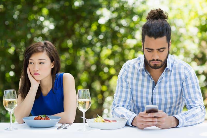 eine Frau, die gelangweilt aussieht, während sie in der Nähe eines Mannes sitzt, der während des Mittagessens im Restaurant ein Smartphone benutzt