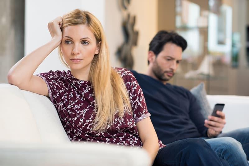 eine Frau, die gelangweilt aussieht während er in der Nähe des Mannes sitzt und sein Telefon benutzt