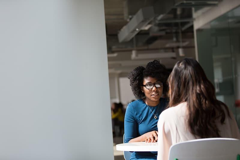 eine Frau, die ihrer Freundin etwas erklärt, während sie am Tisch sitzt