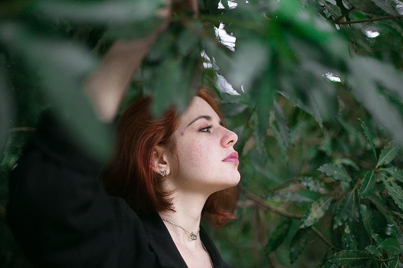eine Frau, die in der Nähe der Bäume steht und nachdenkt