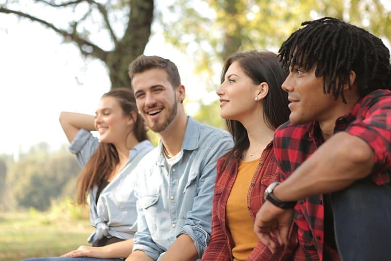 eine Frau, die lächelnden Mann beim Sitzen mit Freunden im Wald betrachtet