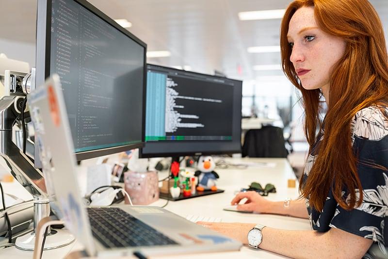 Eine Frau, die mit Arbeit beschäftigt ist und vor dem Computer sitzt