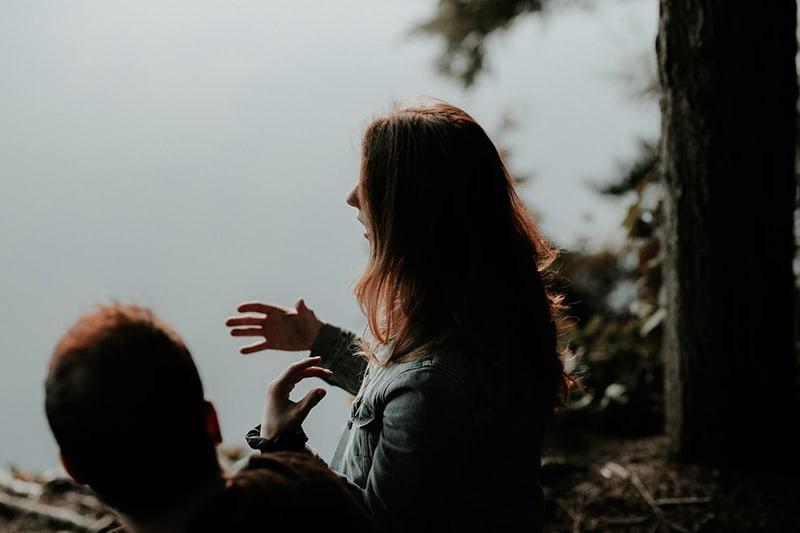 eine Frau, die mit ihren Händen spricht und gestikuliert, während sie mit einem Mann in der Nähe des Gewässers sitzt