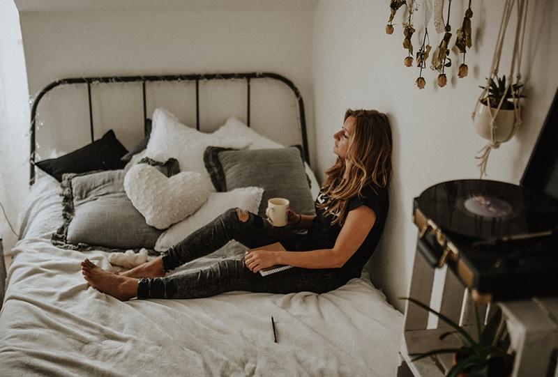 eine Frau, die sich an die Wand lehnt, während sie auf dem Bett sitzt und nachdenklich aussieht