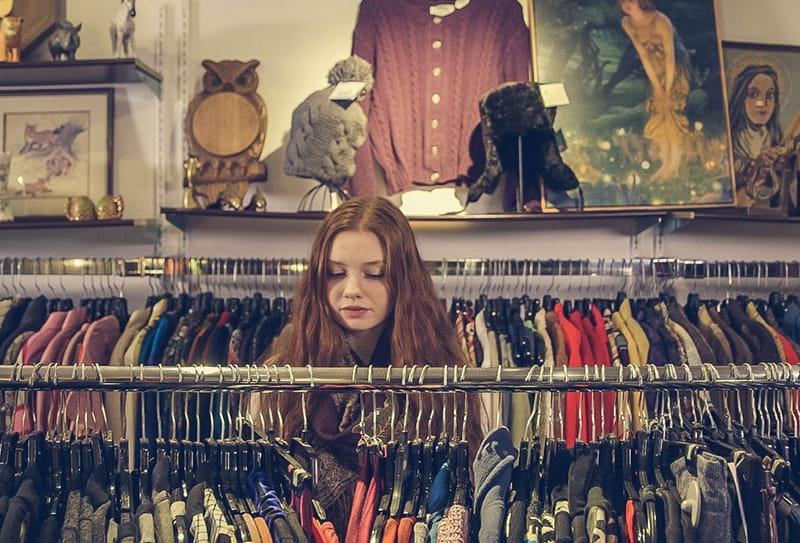 eine Frau, die vor Kleidern im Laden steht