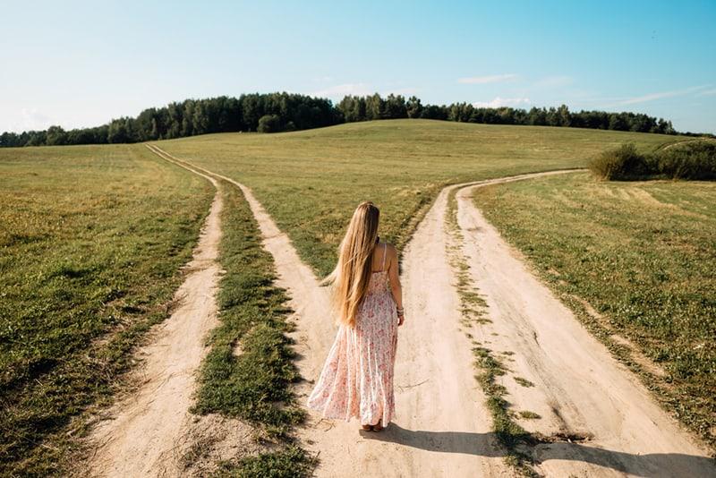 eine Frau, die vor zwei Straßen steht und entscheidet, welchen Weg sie gehen soll