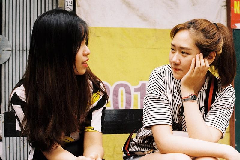 eine Frau, die zuhört und ihre Freundin ansieht, während sie auf der Bank sitzt