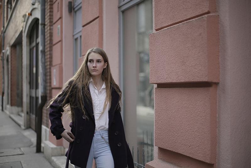 eine Frau in einem Mantel, die auf dem Bürgersteig in der Nähe der Gebäude geht
