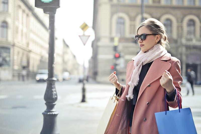 eine Frau in einem rosa Mantel, der eine Einkaufstasche hält, die auf der Straße steht