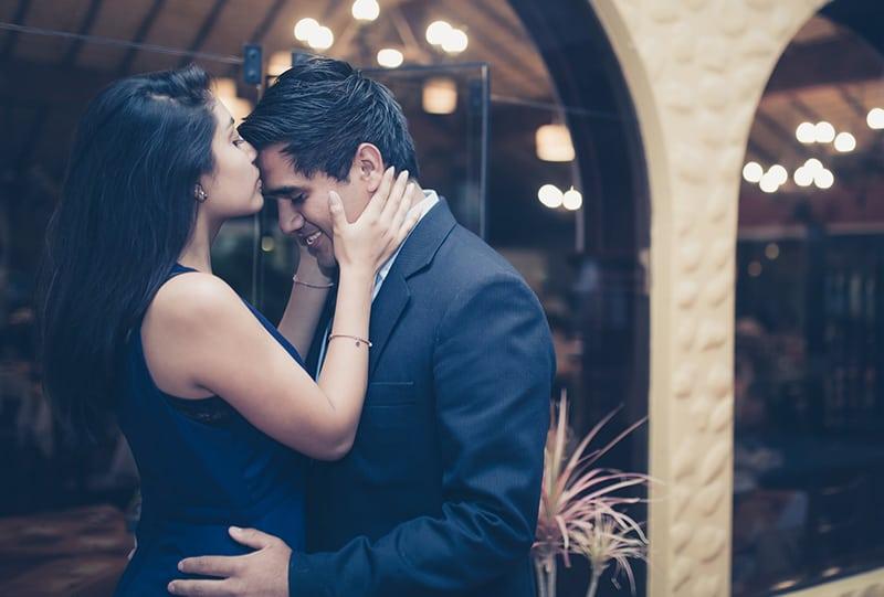 eine Frau küsst die Stirn eines Mannes, während er sie um die Taille hält