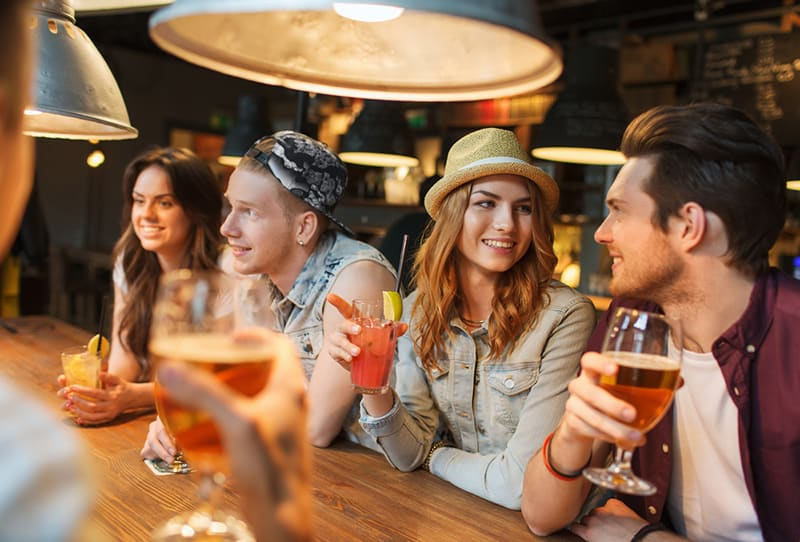 a woman wearing a hat flirting with a man while sitting by the counter bar with friends