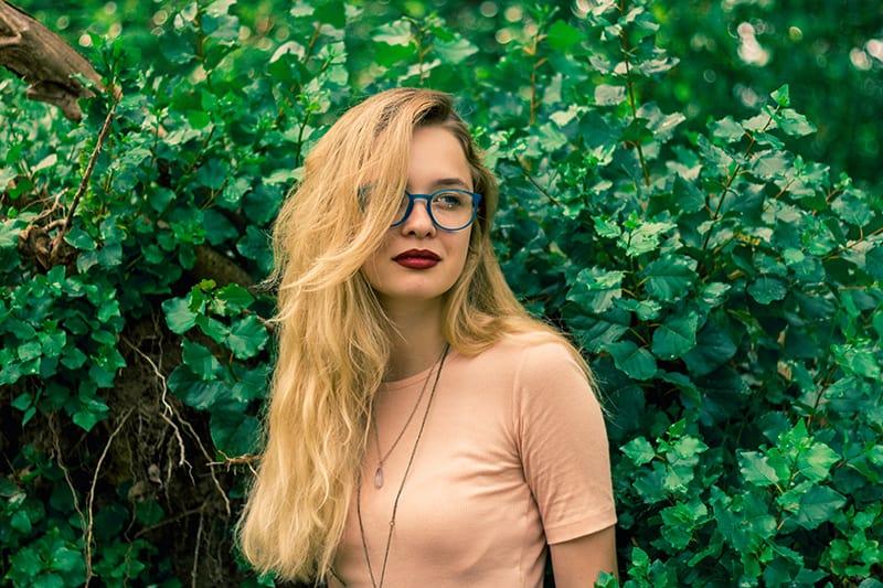 eine Frau mit Sonnenbrille, die beiseite schaut, während sie in der Nähe von grünen Pflanzen steht