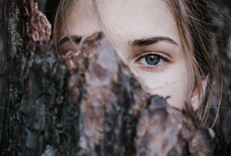 eine Frau mit blauen Augen versteckt sich hinter dem Baum
