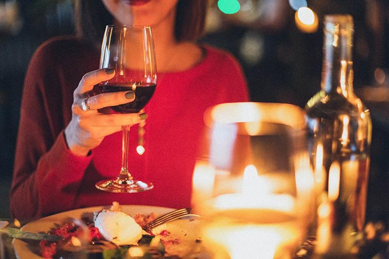 eine Frau, die beim Abendessen ein Glas Wein in der Hand hält