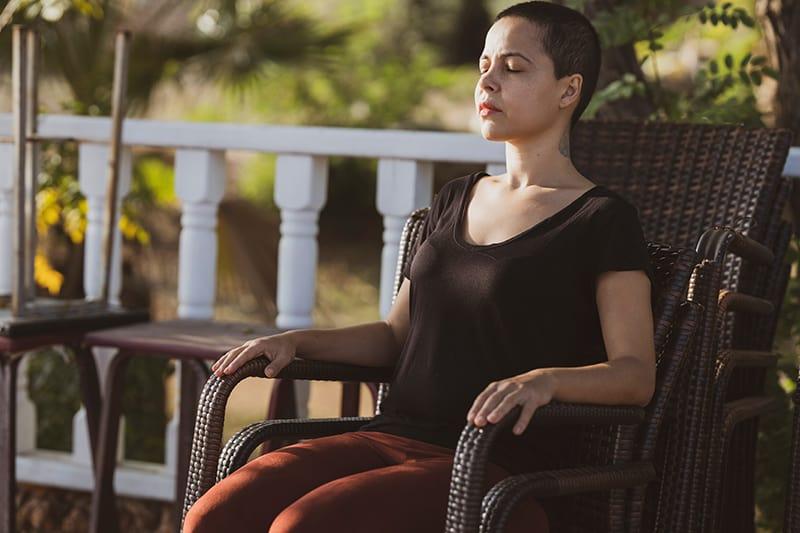 Eine Frau mit geschlossenen Augen sitzt im Sessel und macht eine Pause