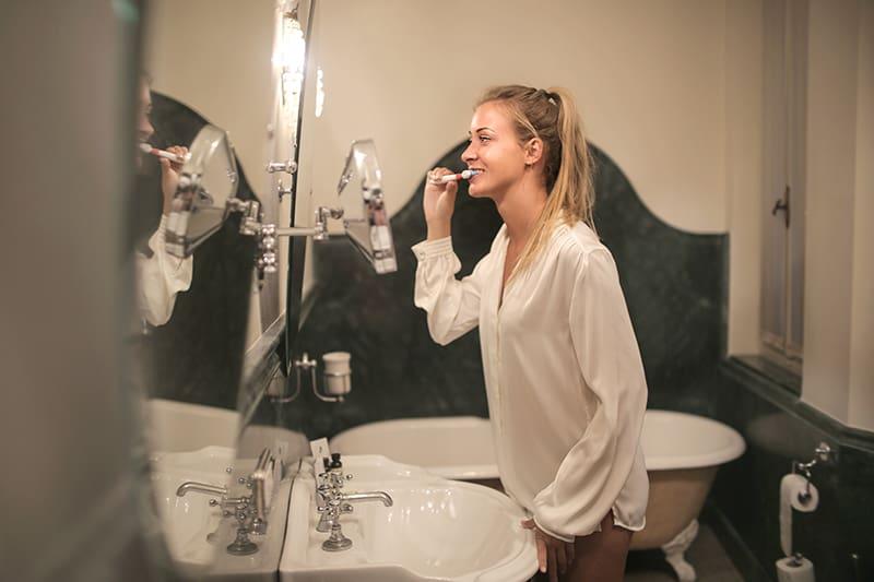Eine Frau putzt sich die Zähne, während sie im Badezimmer vor dem Spiegel steht