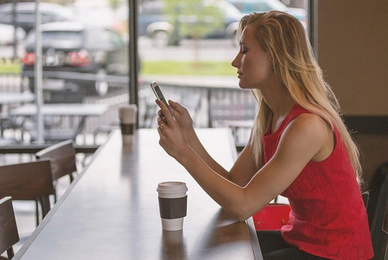 eine Frau, die an der Theke sitzt und ein Smartphone benutzt