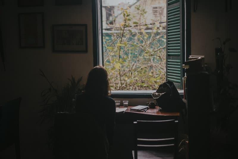 eine Frau sitzt an einem Schreibtisch in einem Raum