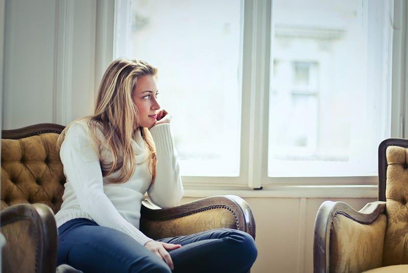 eine Frau, die auf dem Sessel sitzt und nachdenkt