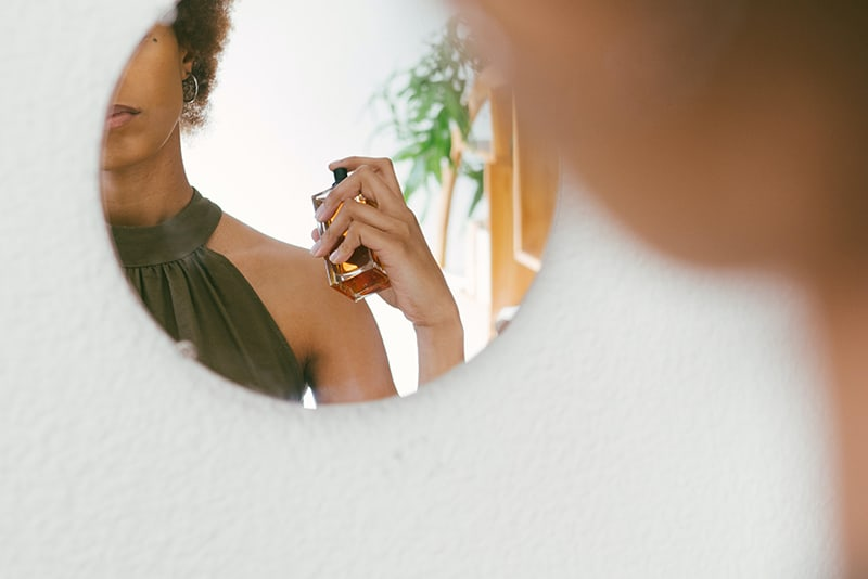 Eine Frau sprüht Parfüm auf ihren Körper, während sie vor dem Spiegel steht