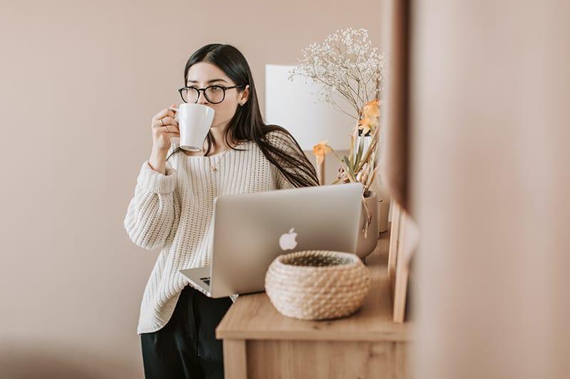 eine Frau, die einen Kaffee trinkt, während sie in der Wohnung steht