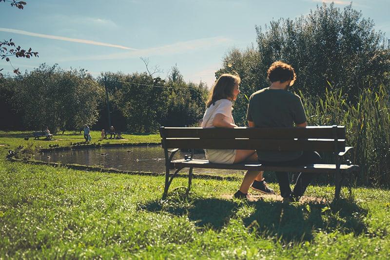 Eine Frau und ein Mann sitzen während des Dates auf der Bank in der Nähe des Sees im Park
