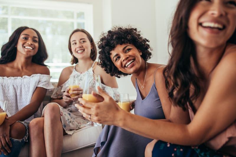 Eine Gruppe einer Freundin kichert zusammen, sitzt auf der Couch und schaut in die gleiche Richtung