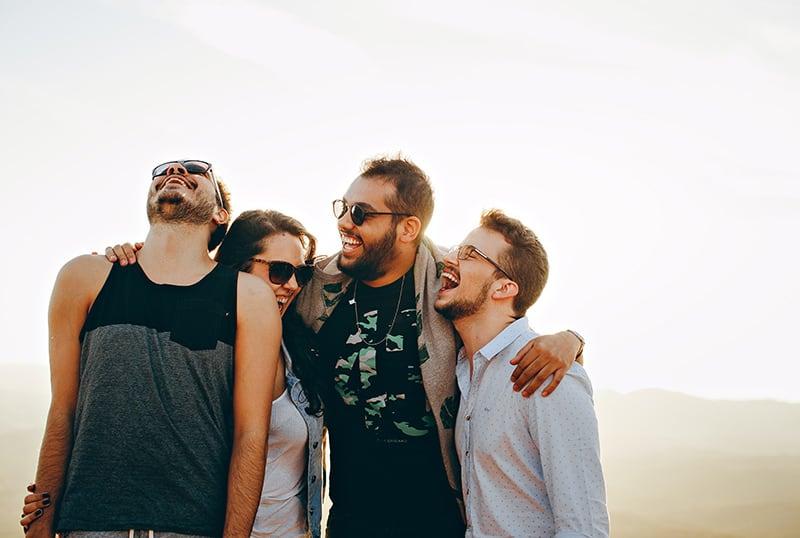 eine Gruppe lächelnder Freunde, die sich umarmen