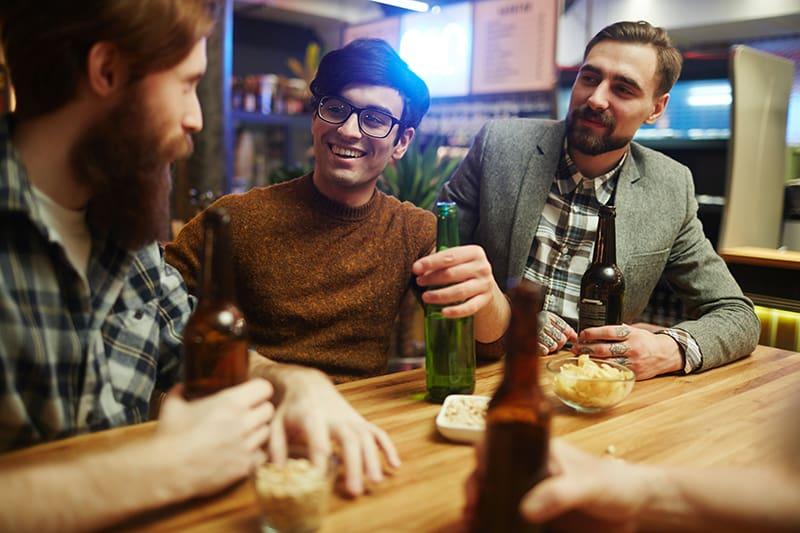 eine Gruppe männlicher Freunde, die lächeln und reden, während sie in der Bar trinken