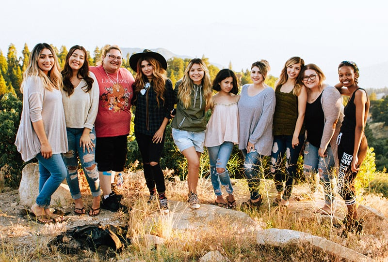 eine Gruppe von Frauen, die auf dem Felsen stehen und für das Foto posieren